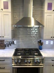 new oven installation with overhead hood and grey backsplash